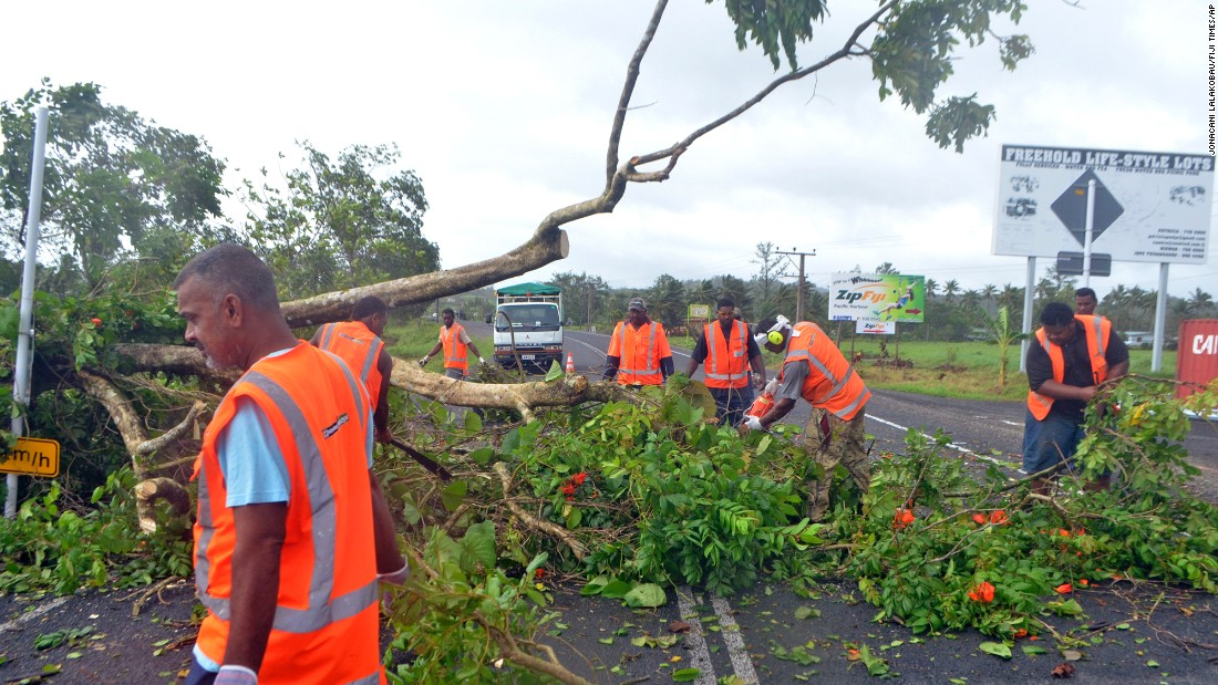 Road workers remove a fallen tree blocking a road near Lami, Fiji, on Sunday, February 21, after Cyclone Winston ripped through the country.