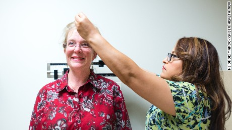 Eileen Bachemin, 50, gets her height measured during a physical exam.