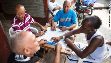 Men play dominoes on the sidewalk of Santo Domingo's Little Haiti neighborhood.