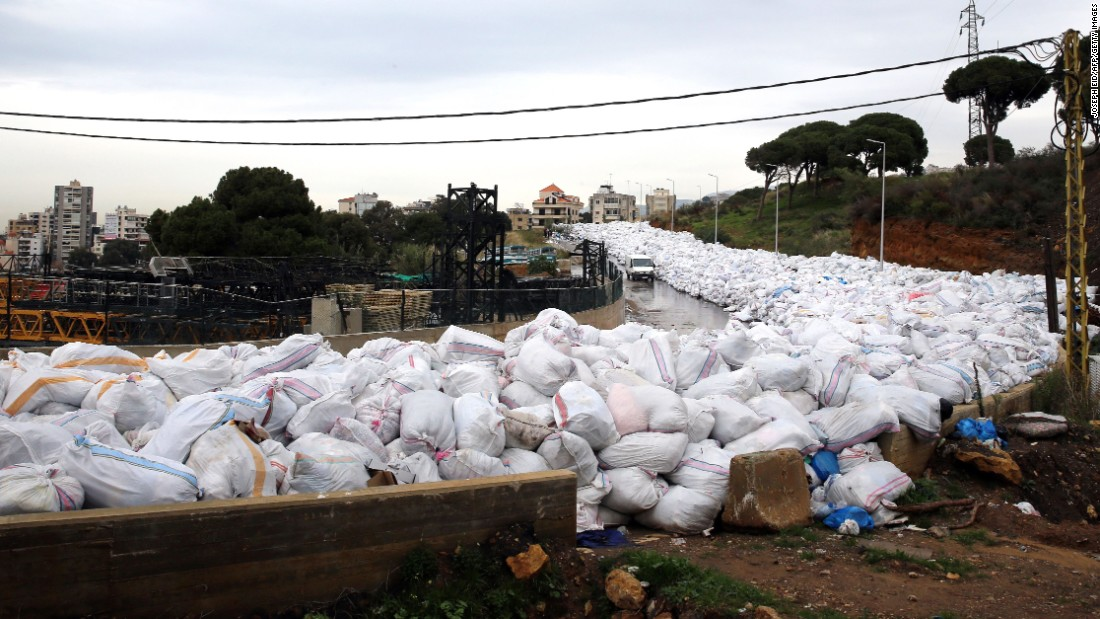 A van drives past piles of garbage blocking a newly opened road in the town of Jdeideh, northeast of Beirut, on January 4.