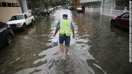 Howard Rogers walks through a flooded street in Miami Beach in September 2015.