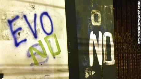 "A man is seen walking next to a graffiti that reads ""Evo no"" after the referendum rejection in El Alto, Bolivia, on February 21. Bolivians on Sunday rejected leftist President Evo Morales' bid to seek a fourth term and potentially extend his presidency until 2025, local media reported. AFP/PHOTO/Aizar Raldes / AFP / AIZAR RALDES        (Photo credit should read AIZAR RALDES/AFP/Getty Images)"