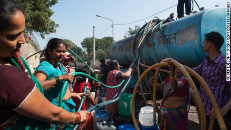 Indian residents remove hoses from a water distribution truck at a distribution point in the low-income eastern New Delhi neighborhood of Sanjay camp on February 23, 2016.