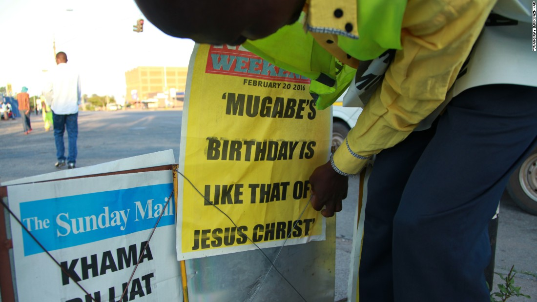 A newspaper vendor in Harare places a banner describing  Zimbabwean President Robert Mugabe's birthday as being like that of Jesus Christ, on Sunday, February 21, 2016.