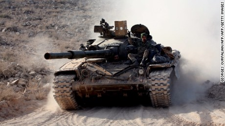 "Syrian government forces drive a tank on a road during a military operation against the Islamic State (IS) group in the villages of Zarour and Khanaser, in the Aleppo governorate, on February 26, 2016.  With the ceasefire due to take effect at 2200 GMT, US President Barack Obama has warned Damascus and key ally Moscow that the ""world will be watching"". Both President Bashar al-Assad's regime and the main opposition body have agreed to the deal -- which allows fighting to continue against the Islamic State group and other jihadists.  / AFP / GEORGES OURFALIAN        (Photo credit should read GEORGES OURFALIAN/AFP/Getty Images)"