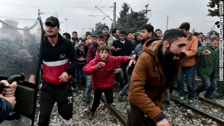 "Migrants run after breaking Greek police blockade towards the border fence of Macedonia near the Greek village of Idomeni, on February 29 , 2016.Macedonian police fired tear gas on February 29, 2016, as a group of some 300 Iraqi and Syrians forced their way through a Greek police cordon and raced towards a railway track between the two countries. With Austria and Balkan states capping the numbers of migrants entering their soil, there has been a swift buildup along the Greece-Macedonia border with Athens warning that the number of people ""trapped"" could reach up to 70,000 by next month."