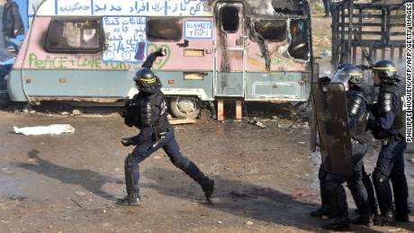 "A police officer throws a tear gas canister during the dismantling of half of the ""Jungle"" migrant camp."