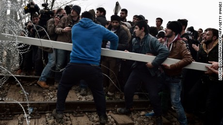 Migrants ram the border fence between Greece and Macedonia at a camp near the village of Greek village of Idomeni.