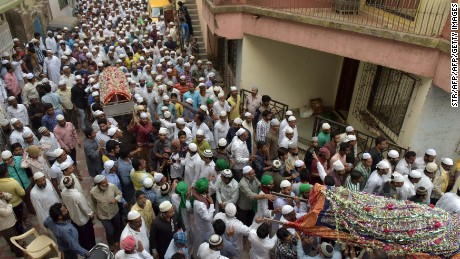 Indian mourners bear the coffins of some of the 14 family members murdered in Thane during their funeral Sunday.