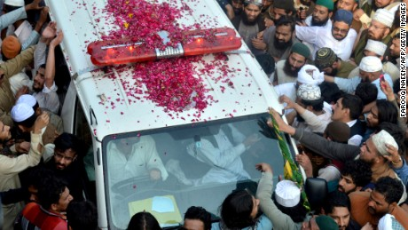 Qadri's supporters gather around the ambulance carrying his body.
