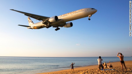 """Each year, I take several trips to enjoy a spot of aviation photographing,"" says plane-spotter Kok Chwee Sim. ""This picture was taken end-December 2015 at Phuket International Airport. When the planes land from the west, they swoop low over the beach and this is a thrill for beachcombers and aviation spotters. The plane depicted here is a B777-300ER of Etihad Airways."""