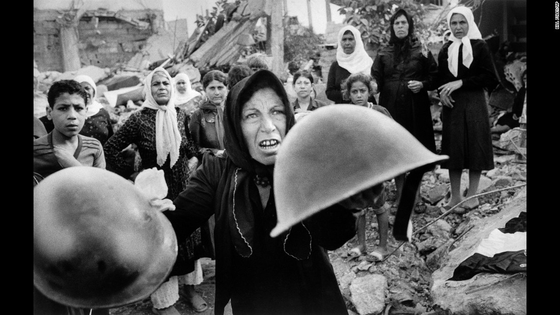 <strong>Sabra and Shatila massacre: </strong>In this Pulitzer Prize-winning photo taken September 27, 1982, by Associated Press photographer Bill Foley, a woman holds up helmets that she believes were worn by those who killed hundreds of Palestinians at the Sabra and Shatila refugee camps during the 1982 Israel-Lebanon war. The murders were committed by Lebanese militia members, but an Israeli government inquiry determined Israel was complicit in the massacre.