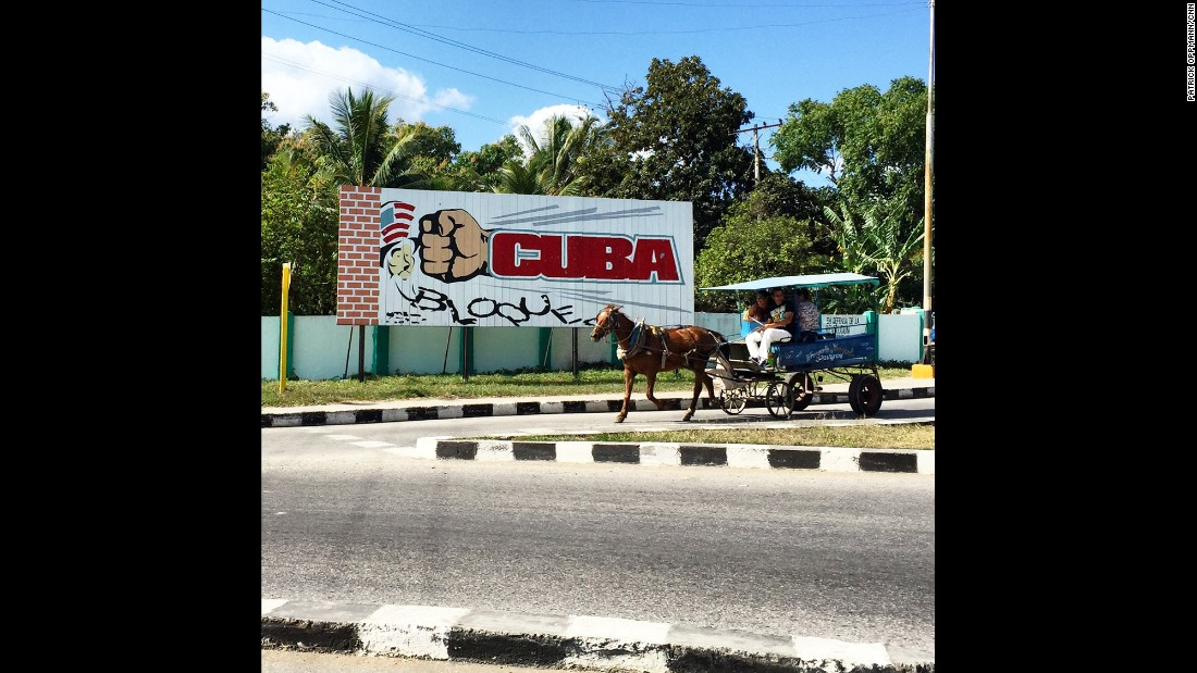 "CUBA: ""A horse drawn carriage in Cienfuegos travels past a billboard calling for an end to US sanctions on the island. Cuban government propaganda still paints the US as a hostile force but officials here have said they welcome President Obama's visit to the island next month. Almost every Cuban I know is excited for the long delayed thaw in relations that is happening before their very eyes."" - CNN's Patrick Oppmann <a href=""http://instagram.com/cubareporter"" target=""_blank"">@cubareporter</a>."