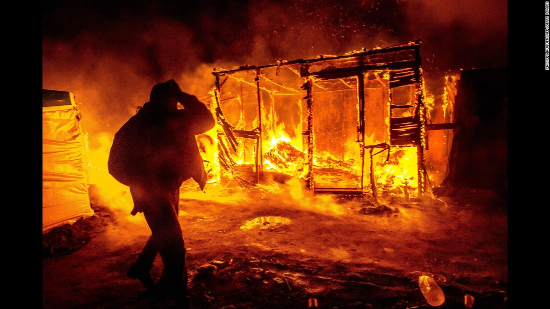 "A migrant walks past a burning shack in the southern part of the ""Jungle"" migrant camp in Calais, France, in March 2016. Part of the camp was being demolished -- and the inhabitants relocated -- in response to unsanitary conditions at the site."
