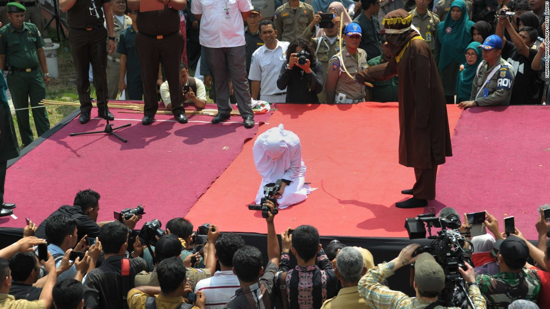 "A Sharia policeman canes a young woman in Banda Aceh, Indonesia, on Tuesday, March 1. The woman was one of 18 people being publicly caned for breaking Islamic law. <a href=""http://tribune.com.pk/story/1057049/unmarried-muslim-couple-publicly-caned-in-indonesia-for-spending-time-alone-together/"" target=""_blank"">According to Agence France-Presse,</a> the woman and a man were punished for spending time alone together -- something that is illegal there for unmarried Muslim couples."