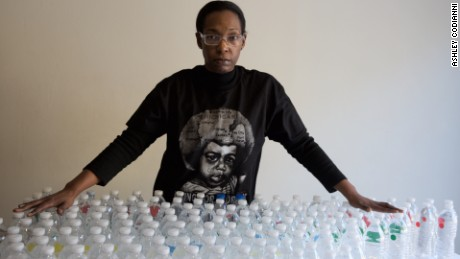 Gina Luster in her Flint, Michigan home with the total bottles of water it takes to get through a day.