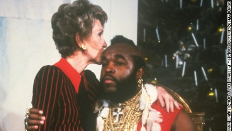 First lady Nancy Reagan sitting on lap & kissing Mr. T done up as Santa Clas at WH Christmas decoration tour.  (Photo by Diana Walker//Time Life Pictures/Getty Images)