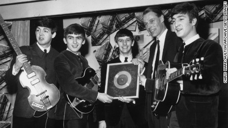 8th April 1963:  British pop group The Beatles holding their silver disc. Left to right are, Paul McCartney, George Harrison (1943 - 2001), Ringo Starr, George Martin of EMI and John Lennon (1940 - 1980).
