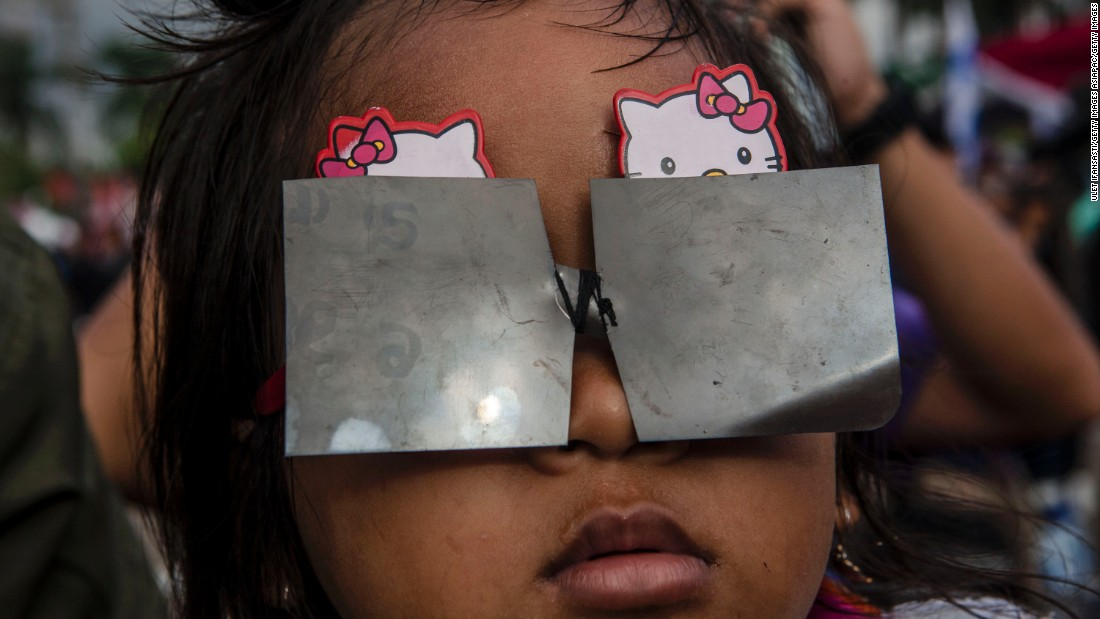 A young girl in Palembang city wears a protective filter to shield her eyes while watching the eclipse.