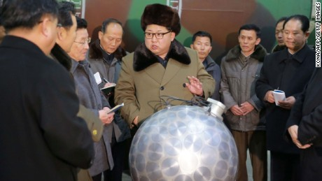 In an undated photo, Kim Jong Un gathers with nuclear weapons scientists and technologists around what North Korea claimed was a miniaturized nuclear warhead.