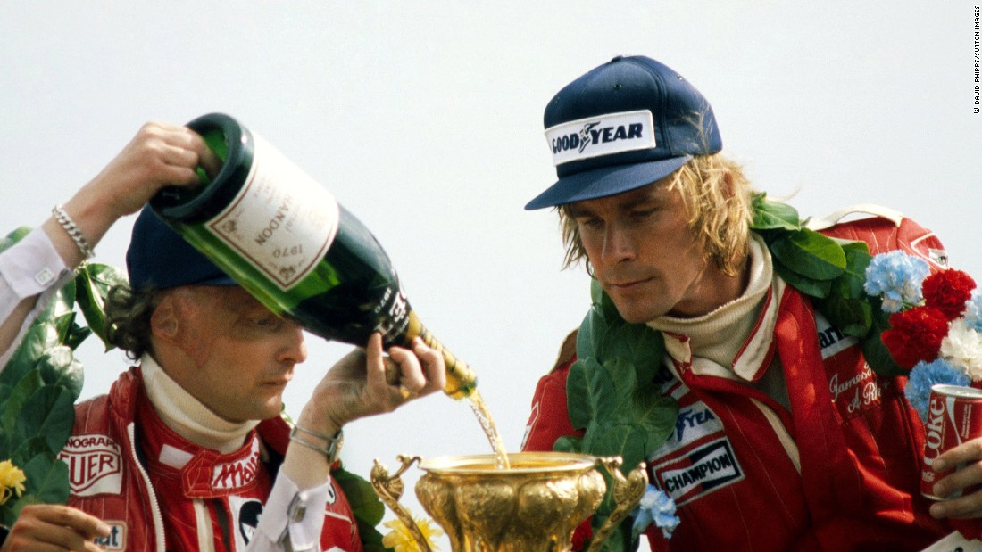 Lauda watches as champagne is poured into Hunt's trophy at the 1977 British Grand Prix at Silverstone.