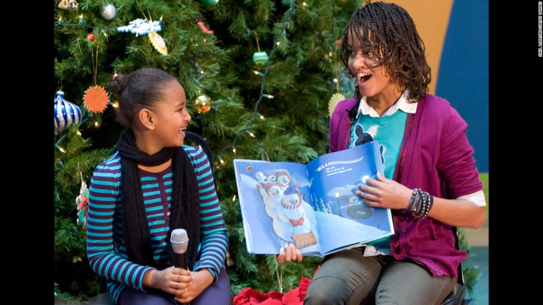 Malia and Sasha read a book to children during a visit to a hospital in Washington in December 2009.