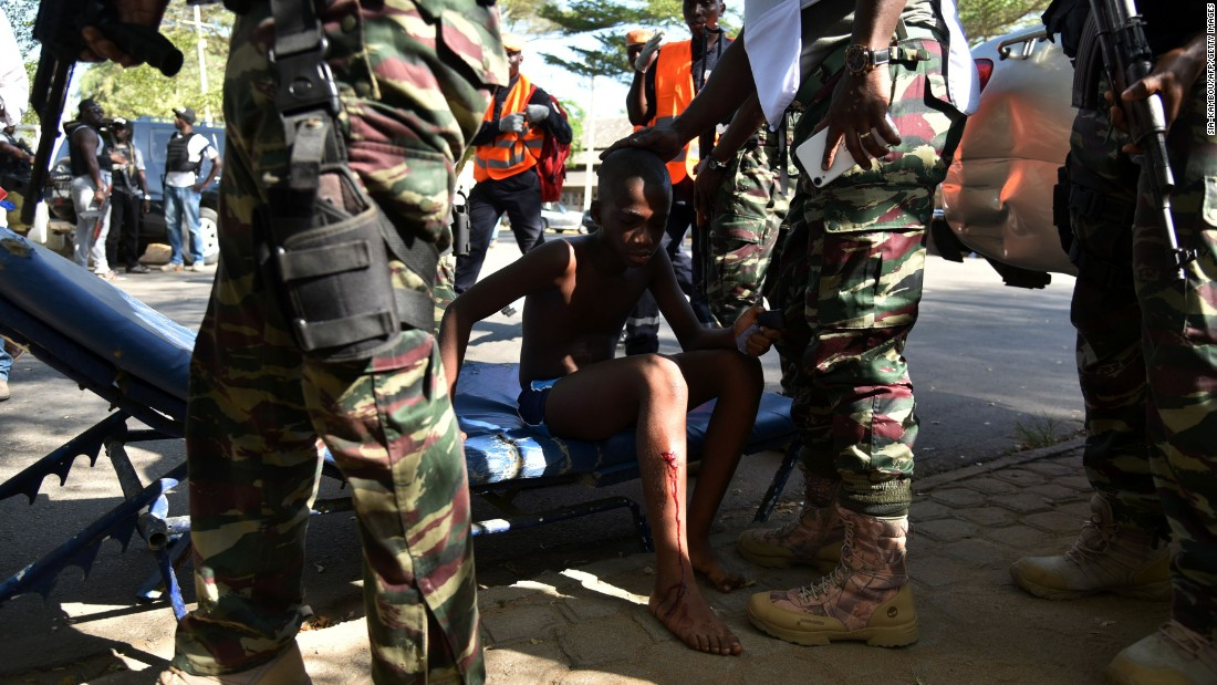 Ivorian soldiers stand around a boy who was injured.