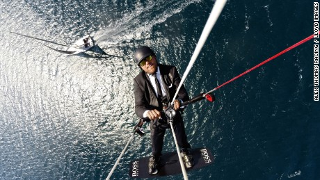 Thomson kite surfs high above his Hugo Boss yacht in a publicity stunt.