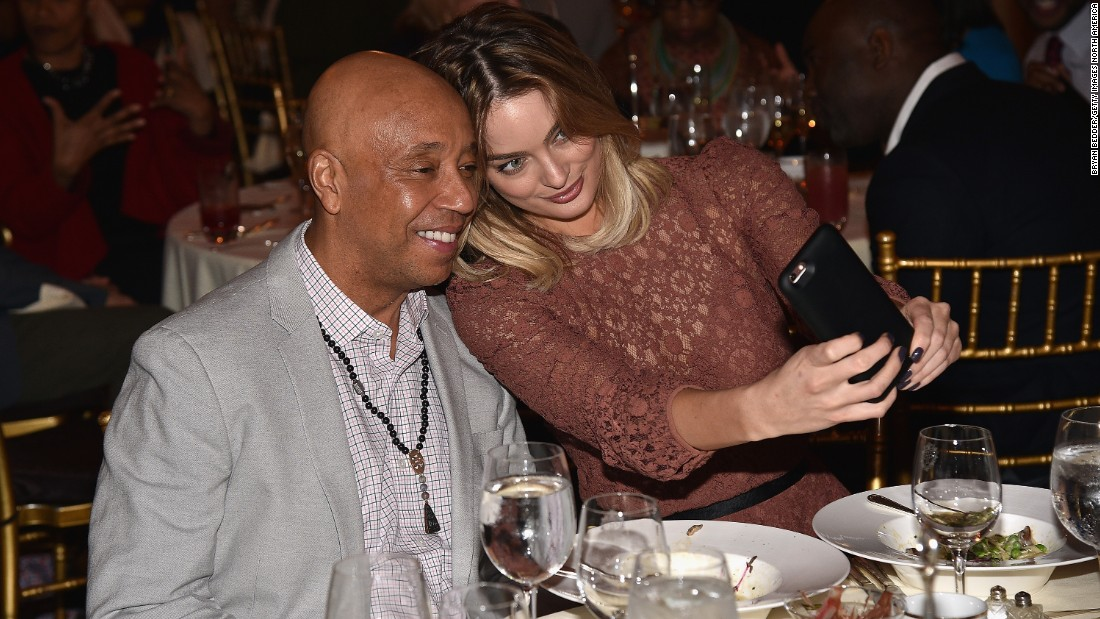 Model Lucy McIntosh takes a photo with her boyfriend, hip-hop mogul Russell Simmons, during a luncheon Friday, March 11, that raised money for the Rush Philanthropic Arts Foundation.