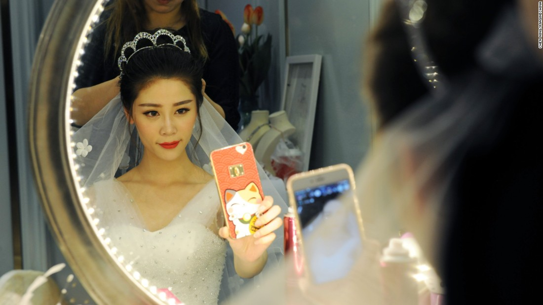 A model wearing a bridal gown takes a selfie before a promotional event in Jinan, China, on Sunday, March 13.