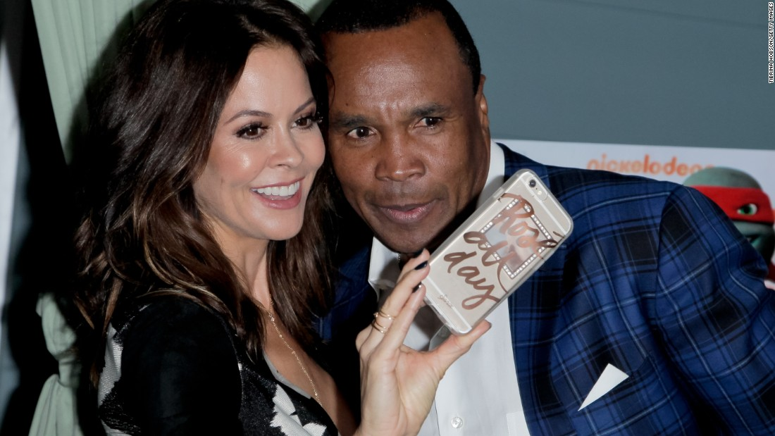 Actress Brooke Burke-Charvet snaps a photo with boxing legend Sugar Ray Leonard at a charity event in Manhattan Beach, California, on Thursday, March 10. Skechers' Pier to Pier Friendship Walk raised money for public education and children with special needs.