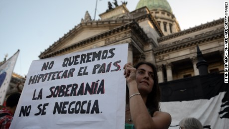 People demonstrate outside the National Congress in Buenos Aires, on March 15, 2015, against the bill brokered by Argentine President Mauricio Macri's administration, aimed at putting an end to Argentinas long-standing legal battle against so called vulture funds suing the country over its defaulted bonds more than a decade ago. The bill must be approved by the Congress.  AFP PHOTO / EITAN ABRAMOVICH / AFP / EITAN ABRAMOVICH        (Photo credit should read EITAN ABRAMOVICH/AFP/Getty Images)