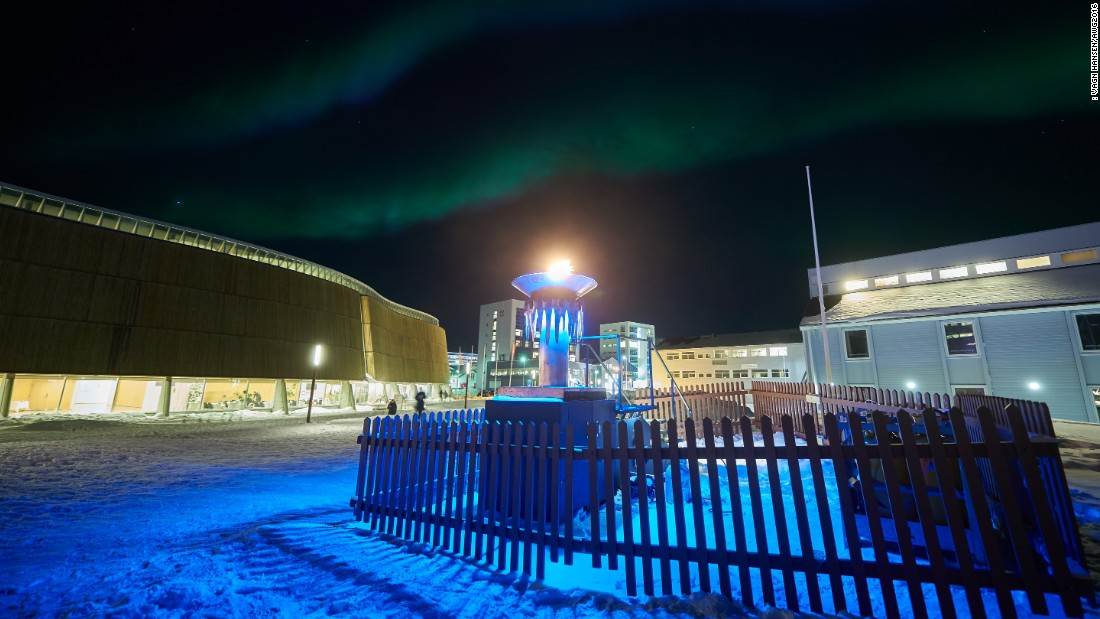 The northern lights flicker above the burning flame of the Arctic Winter Games in the center of Nuuk.