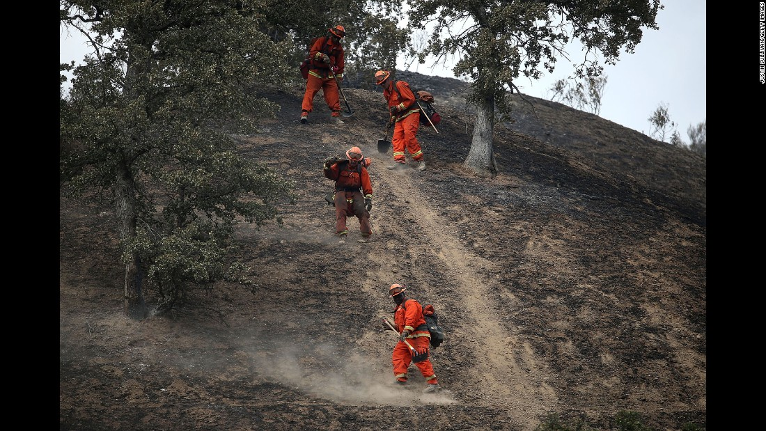 Firefighters hike down a hill in Clearlake, California, as they mop up hot spots from the Rocky Fire in August.