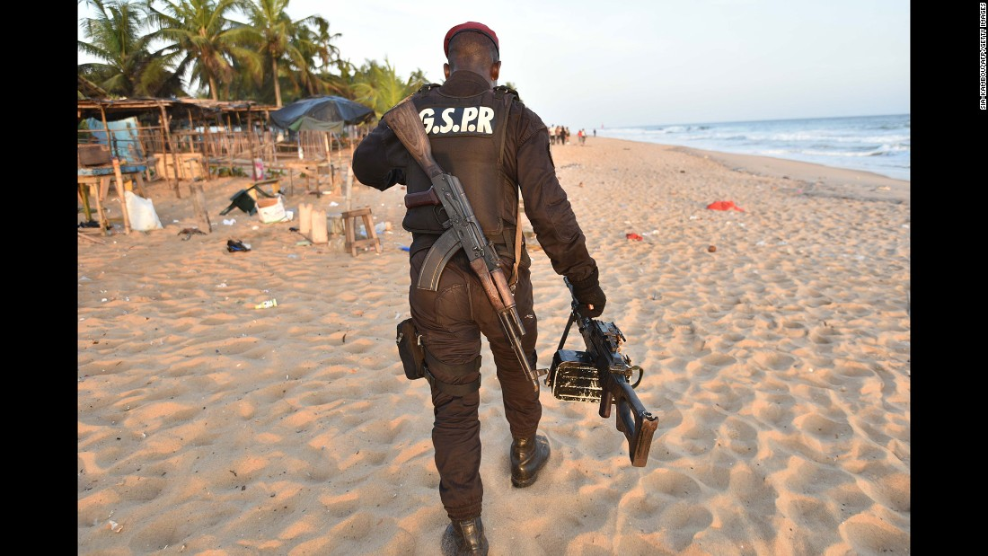 An Ivorian soldier carries a machine gun as he walks on the beach. Three terrorists also were killed, the Ivory Coast presidency said on its Facebook page, citing Interior Minister Hamed Bakayoko.