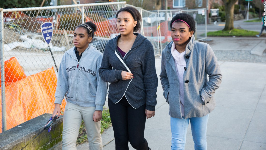 Marcelas takes a walk with her sisters Myanna, 12, left, and Monique, 13, near their home.