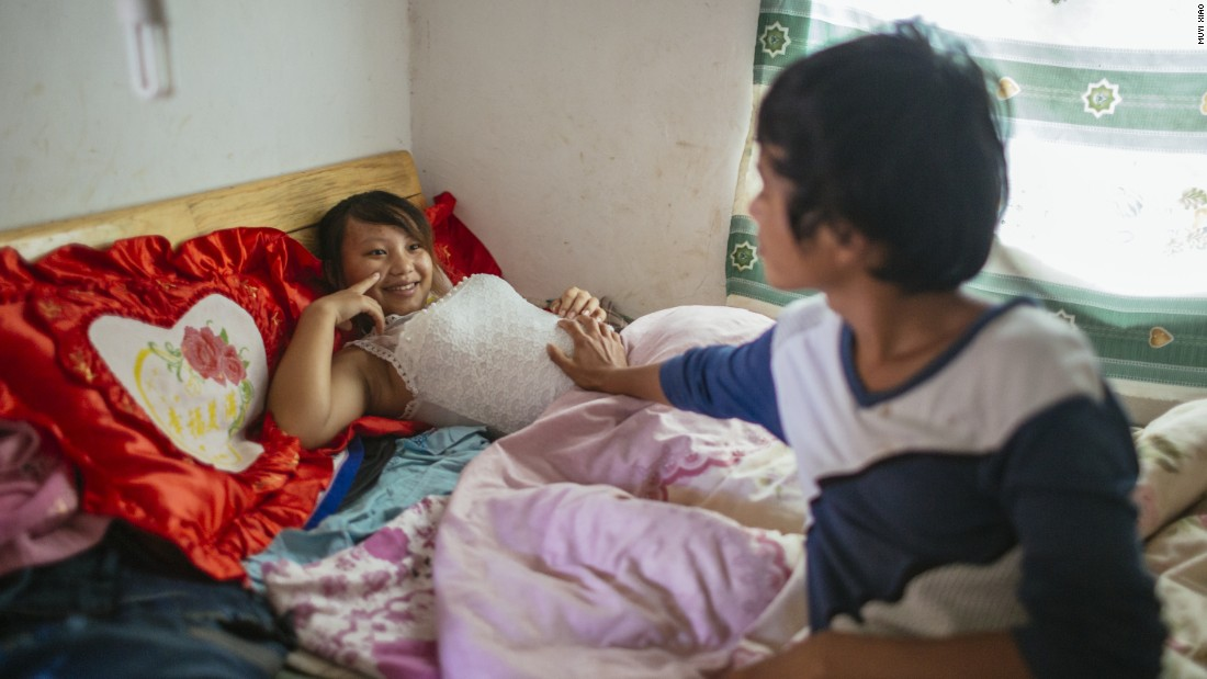 Wen, 18, touches the pregnant belly of his 13-year-old wife Jie. They live together in Tangzibian village, Mengla county in Yunnan.