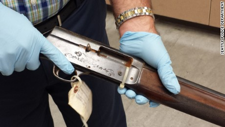 Seattle Police Detective Mike Ciesynski holds shotgun used in Kurt Cobain suicide