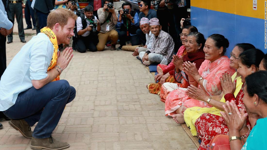 Prince Harry talks to Nepalese women in a community courtyard outside the Golden Temple in Kathmandu, Nepal.