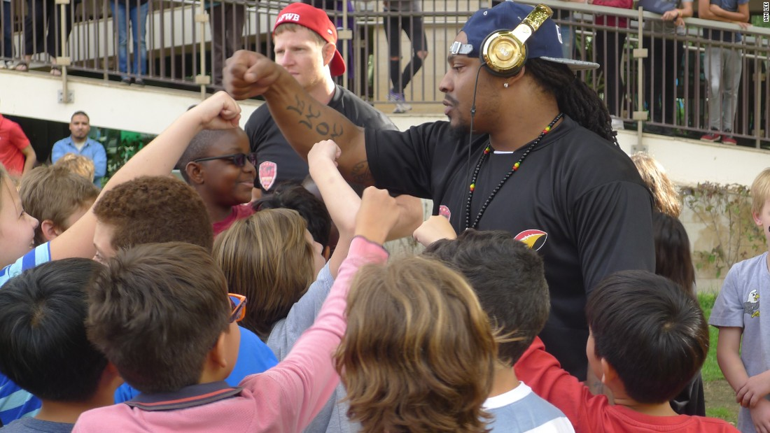 Marshawn Lynch teaches the kids at the camp how to fist bump.
