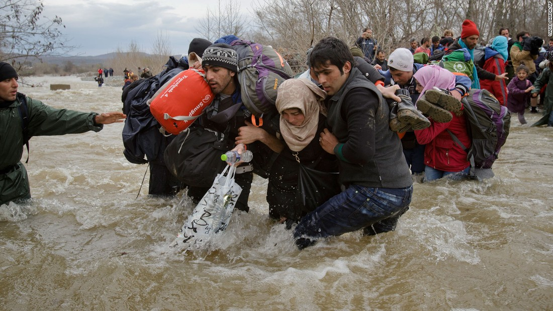 Migrants stumble as they cross a river north of Idomeni, Greece, attempting to reach Macedonia on a route that would bypass the border-control fence in March 2016.
