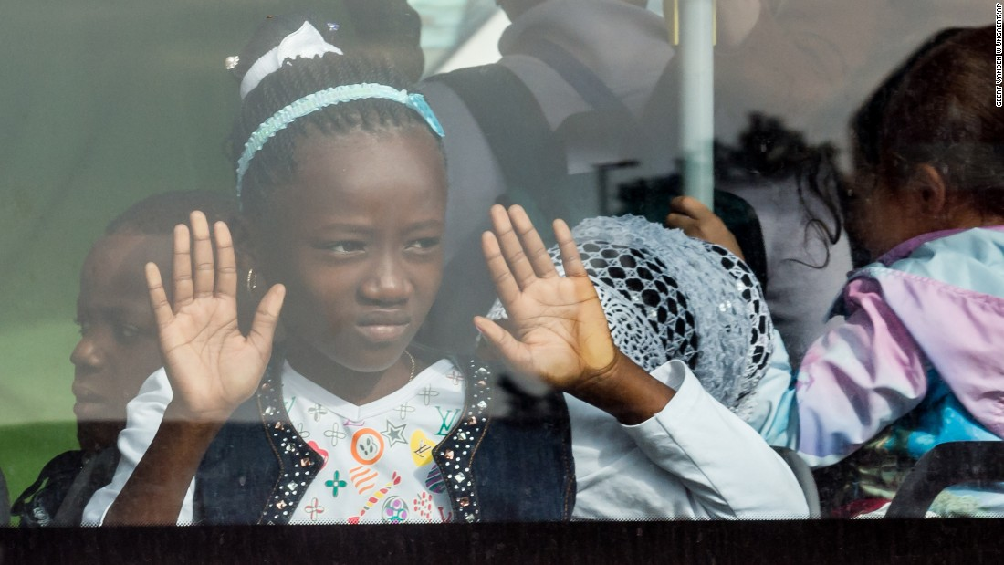 A young girl looks out of the window of a bus after airport evacuations.