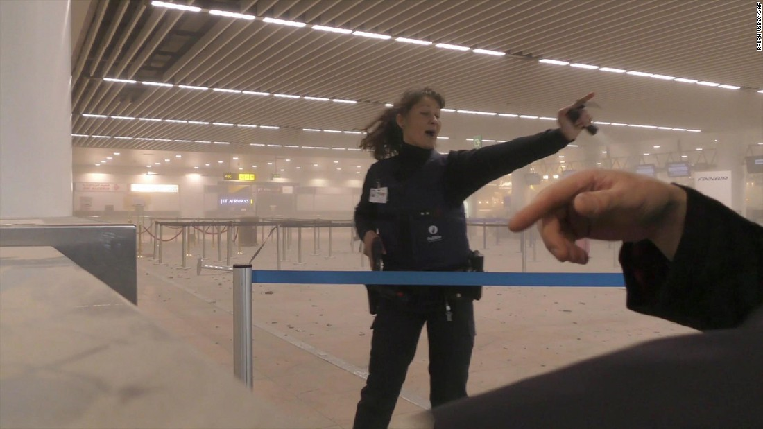 A police officer directs passengers in a smoke-filled airport terminal.