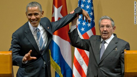 Cuban President Raul Castro tries to lift up the arm of President Barack Obama at the conclusion of their joint news conference at the Palace of the Revolution, Monday, March 21, 2016, in Havana, Cuba.