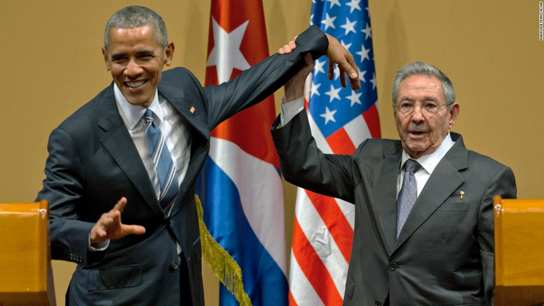 Castro tries to lift up Obama's arm at the end of a joint news conference on March 21.