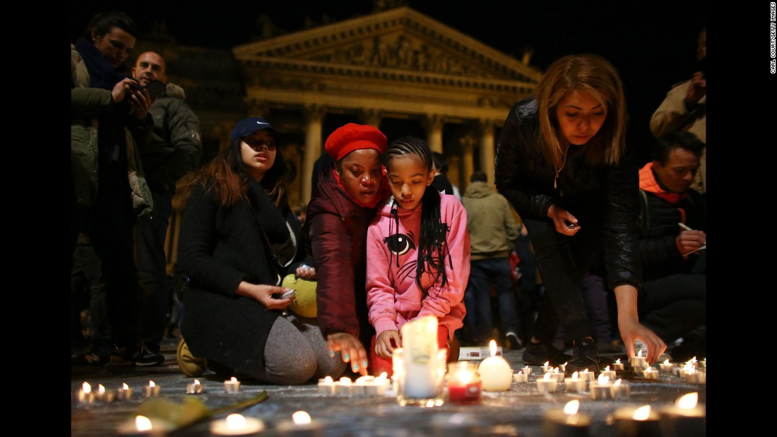 A young girl lights a candle at the Place de la Bourse in Brussels on Tuesday, March 22.