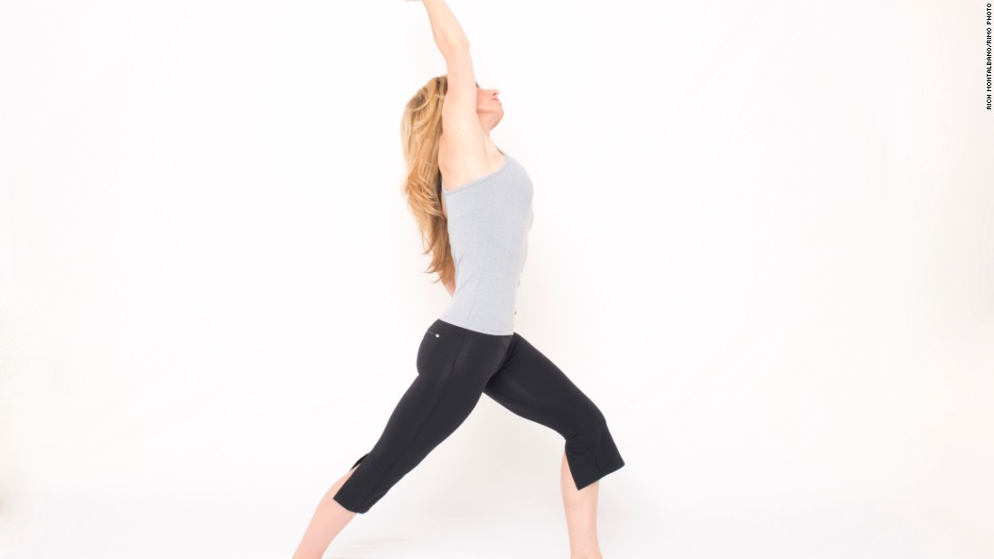 From standing, step your right foot back, as though coming into a lunge, but place your heel down with your toes angled slightly out. Bend your left knee to align above your ankle. Keep your back leg straight. Place your left hand on your left hip. If balance is a challenge, place your left hand on a wall or other support. Inhale as you reach your right arm overhead to the left, stretching your right side and front of your hip. Avoid arching your low back. Hold the stretch for a few breaths. Repeat on the opposite side.