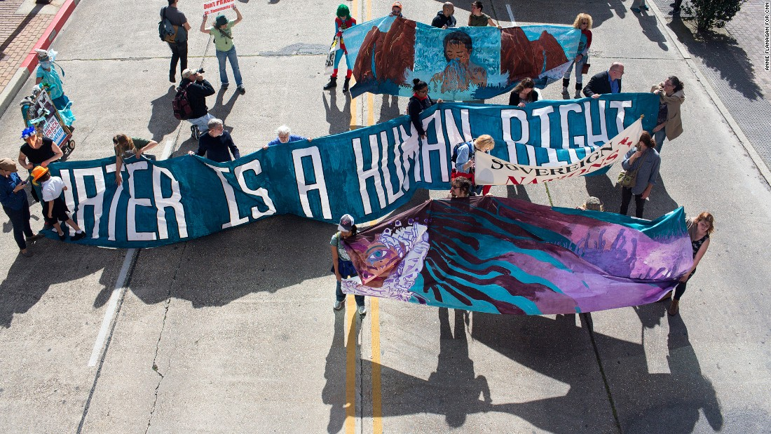 "Climate activists marched on the Superdome carrying signs that said ""Keep it in the ground"" and ""Solar doesn't spill."" Louisiana has been hit hard by environmental disasters, from Hurricane Katrina to the BP oil spill."