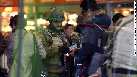 A soldier checks the identification of a person entering Brussels Midi train station.