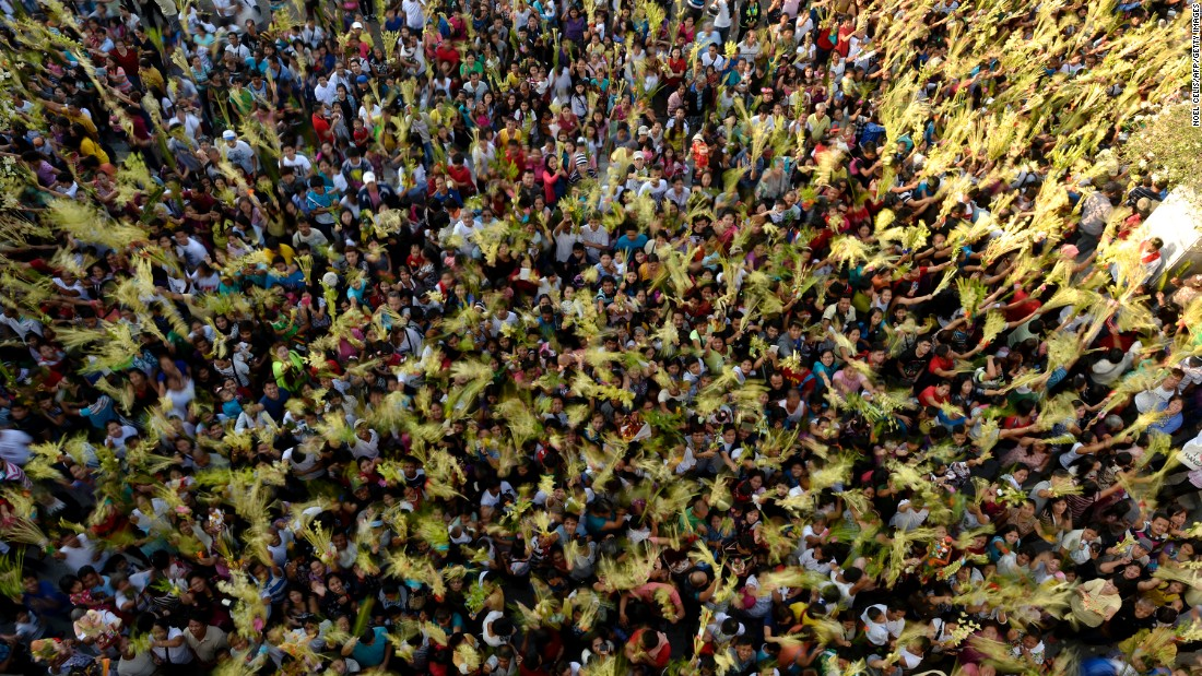 People wave palm fronds during a Palm Sunday Mass in Bulacan, Philippines, on March 20.